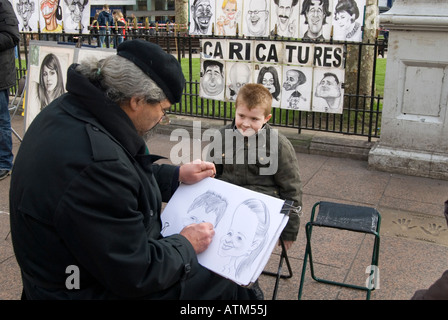 Street artist drawing caricature of small boy in Leicester Square London England UK - Stock Photo