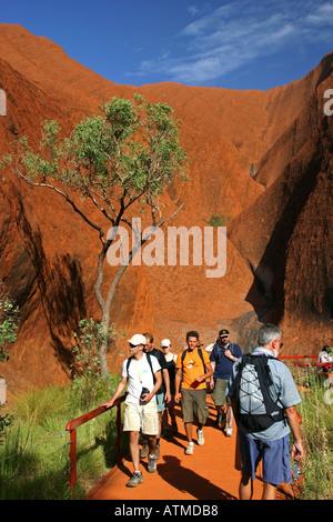 Crowds of tourists walk around the base of famous Ayers rock Uluru on the circular path Northern territory Australia - Stock Photo