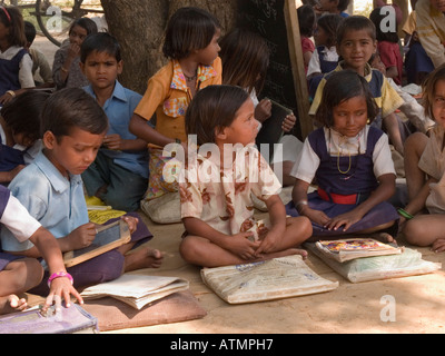 Junior school children sitting on ground with books in shade in rural village for outdoor lesson. Sania Madhya Pradesh - Stock Photo