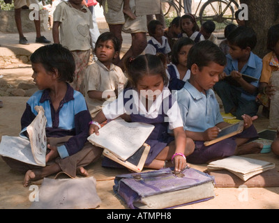 Junior school children sitting on ground with books in shade in rural village for lesson out of doors Sania Madhya - Stock Photo