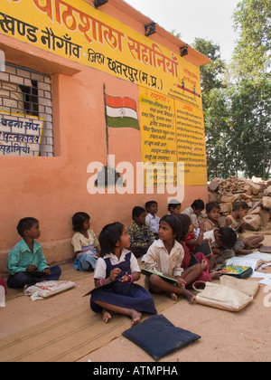 Rows of junior school children sitting on ground in shade outside rural village school for an outdoor lesson. Pradesh - Stock Photo