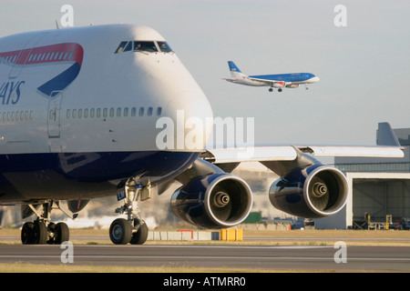 British Airways Boeing 747-436 taxiing and Airbus A319 BMI landing in the background at London Heathrow Airport - Stock Photo