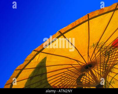 Yellow Asian or Oriental parasol, seen from below, against a clear deep blue sky - Stock Photo