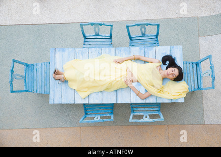 High angle view of a young woman lying on a table - Stock Photo