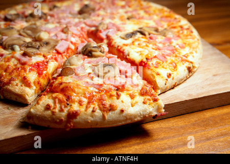 A large Cheese, ham and mushroom Pizza with a slice ready to be eat. Pizza is on a wood board and seems very appetizing - Stock Photo