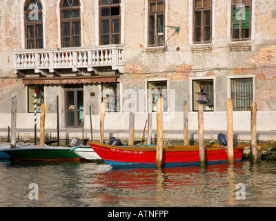 Murano, Venice, Veneto, Italy. Colourful boats moored in front of typical glassworks. - Stock Photo