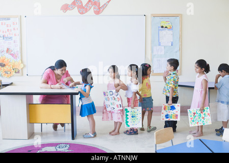 Teacher checking drawings of students in a classroom - Stock Photo