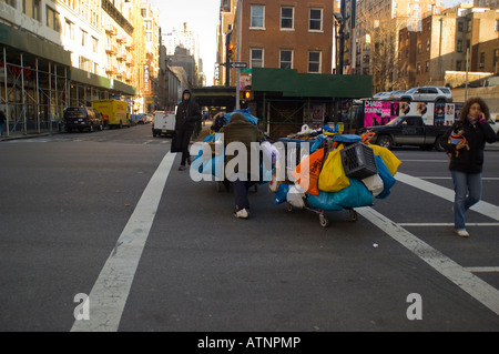 A homeless man crosses Eighth Avenue in the NYC neighborhood of Chelsea with his belongings on shopping carts - Stock Photo