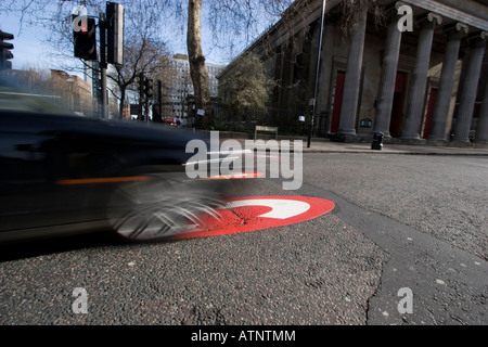 car going through congestion charge zone with giant C in road to signify entry into zone Kings Cross area of London - Stock Photo