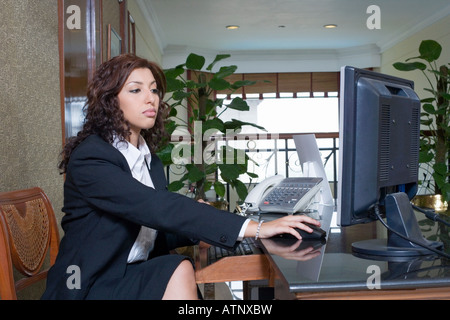 Hotel receptionist working on computer at front desk office stock hotel receptionist working on computer at front desk office side profile of a female receptionist working on a desktop pc in a hotel reception sciox Images