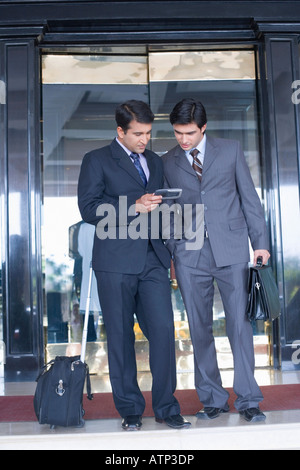 Two businessmen standing in front of the door of a hotel and looking at a mobile phone - Stock Photo