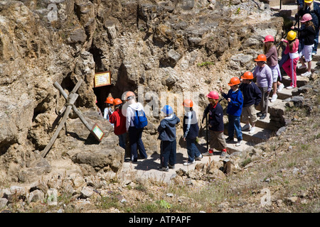 School party entering the underground portion of the Great Orme Ancient Copper Mines excavation Llandudno Wales - Stock Photo