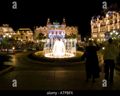Two tourists and the world-famous Monte Carlo Casino at night in Monaco. - Stock Photo
