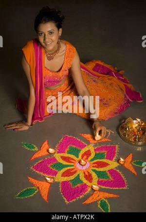 Portrait of a young woman making a rangoli - Stock Photo