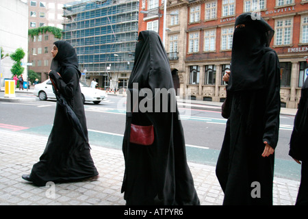 three women walking on a london street on a shopping trip dressed in black in the burka one carrying a handbag - Stock Photo