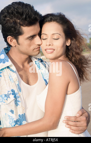Close-up of a young couple romancing on the beach - Stock Photo