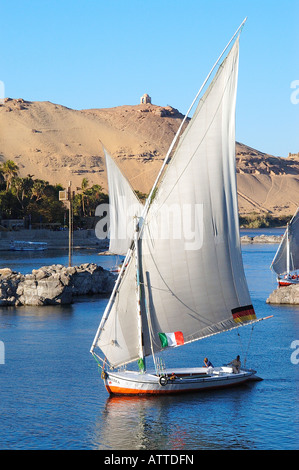 Feluccas, traditional wooden sailing boats  on River Nile at Aswan, Egypt with Aga Khan's mausoleum in background - Stock Photo