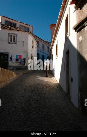 An elderly man walking in the cobbled street leading uphill toward Convento Nossa Senhora De Desterro monastery - Stock Photo