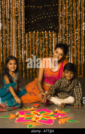 Young woman making a rangoli with her son and daughter - Stock Photo