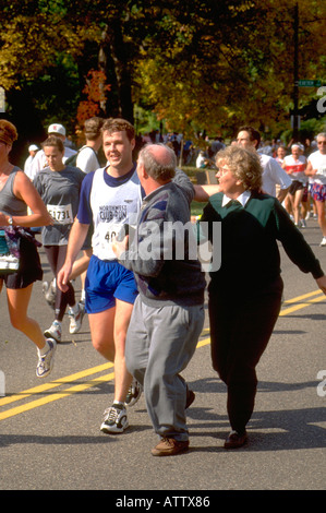 Mother and Father age 55 cheering on son age 22 running in Twin Cities Marathon. St Paul Minnesota USA - Stock Photo