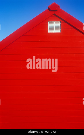 Detail of scarlet red painted wooden beach hut or shed or chalet or kiosk under clear blue sky - Stock Photo