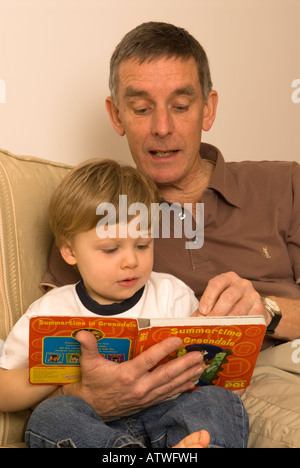 grandfather father reading book to two year old grandson son - Stock Photo