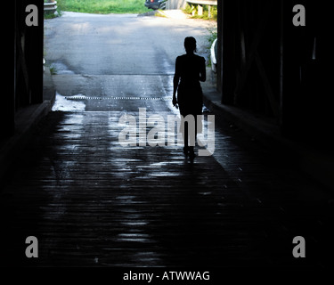 Silhouette of young female walking alone through dark passageway holding car keys - Stock Photo