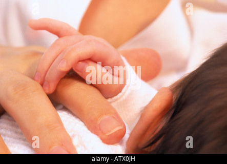 infant's hand resting on mother's hand - Stock Photo