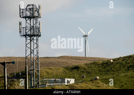 Windmill and mobile phone mast in close proximity in the welsh countryside Ceredigion Wales UK - with a few sheep - Stock Photo
