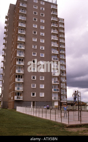 Children playing in front of highrise building. - Stock Photo