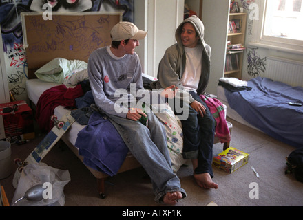 Two teenage friends smoking drinking and chatting in bedroom. - Stock Photo