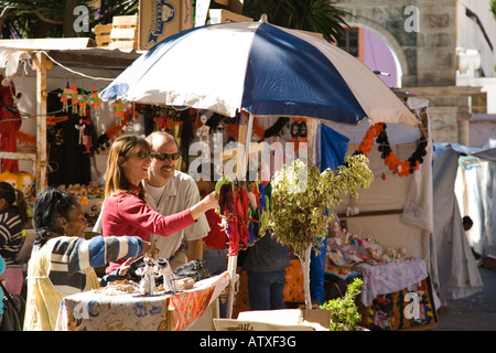 MEXICO Guanajuato Adult man and woman couple shopping for souvenirs at booth in plaza under umbrella Mexican woman - Stock Photo