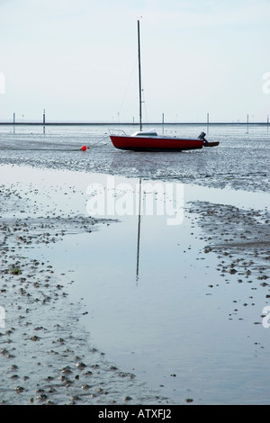 Stranded sailboat on mudflats at low tide in Wadden sea, Juist, Wadden sea national park, Germany - Stock Photo