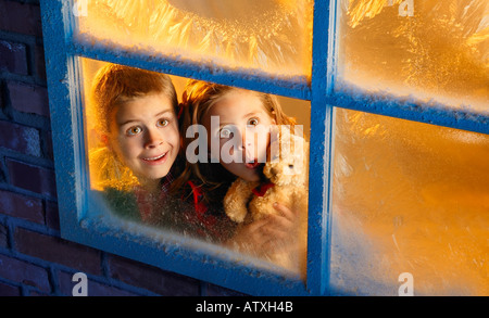 Children looking out window into night sky - Stock Photo