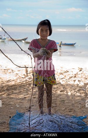 girl removes crabs from nets on Phala Beach, near Rayong, Thailand. - Stock Photo