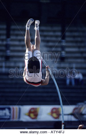 A vaulter stretches to clear the bar in pole vault competition - Stock Photo