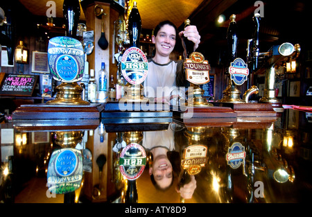 A barmaid pulls an old fashioned pint in a Victorian pub with a copper bar and real ale from handpumps - Stock Photo