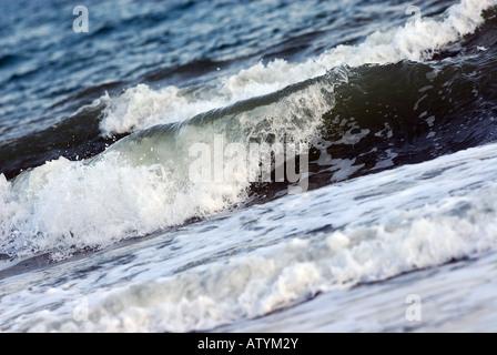 seas waves crashing on the shores coastal breakers rippling ripples white horses waters raging - Stock Photo