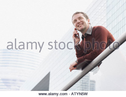 Businessman on balcony using his mobile phone - Stock Photo