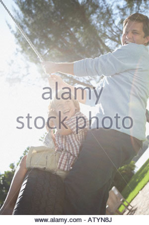 Man and young boy outdoors at park playing on tire swing - Stock Photo