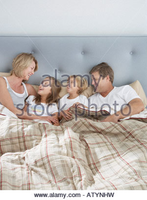 Family in bed together bonding - Stock Photo