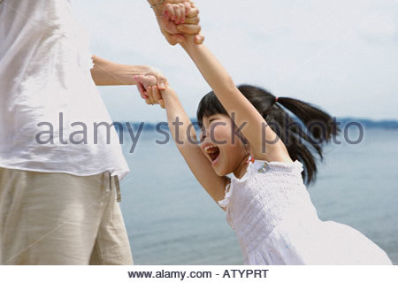 Woman and young girl playing outdoors on beach - Stock Photo