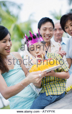 Young boy outdoors celebrating birthday with family - Stock Photo