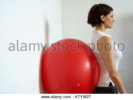 Woman in gym using pilates ball - Stock Photo