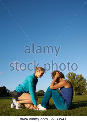 Woman helping another woman do sit-ups outdoors in a park - Stock Photo