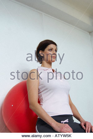 Woman using pilates ball in gym - Stock Photo