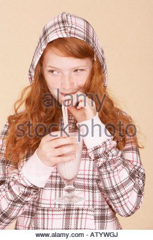 Young girl indoors drinking strawberry milkshake - Stock Photo