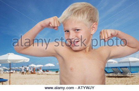 Young boy at the beach flexing biceps - Stock Photo