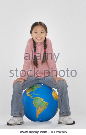 Young girl sitting on a globe indoors - Stock Photo