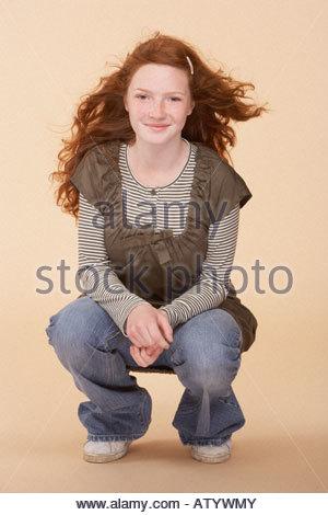Young girl crouching on floor indoors - Stock Photo